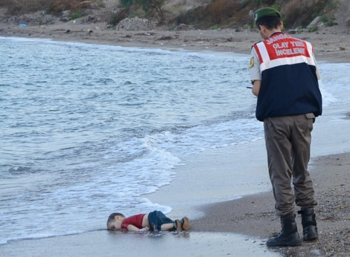 A Turkish policeman discovers the drowned body of young Syrian refugee, presumably drowned as his family tried to flee the war
