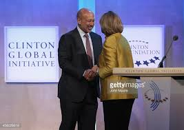 Goldman CEO Lloyd Blankfein is greeted by Hillary Clinton at a meeting of the Clinton Global Initiative. Blankfein and Adams would likely have rubbed shoulders at CGI get-togethers